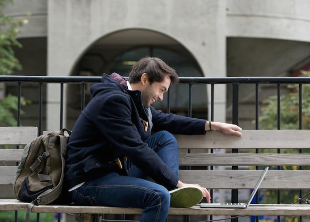 Junger mann, der auf der bank lächelt am laptop sitzt