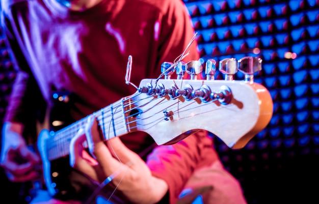 Junger mann, der auf der gitarre im tonaufnahmestudio spielt.