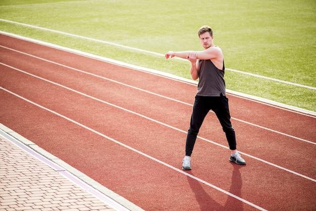 Junger mann, der auf der roten rennstrecke ausdehnt ihre hand steht
