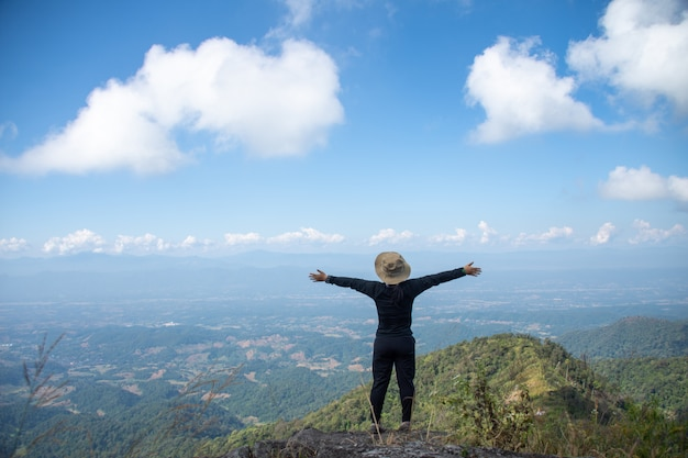 Junger mann, der auf der spitze eines berges steht