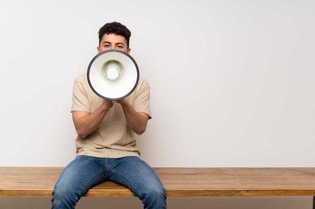 Junger mann, der auf der tabelle schreit durch ein megaphon sitzt