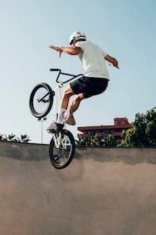 Junger mann, der auf ein bmx-fahrrad im skatepark fährt