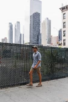 Junger mann, der auf eine gepflasterte straße geht