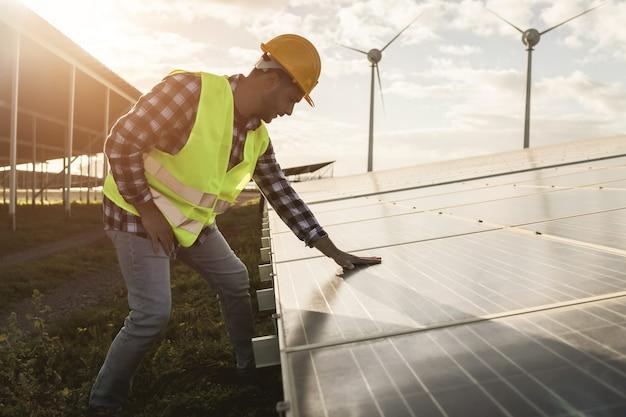 Junger mann, der auf einem bauernhof für erneuerbare energien arbeitet