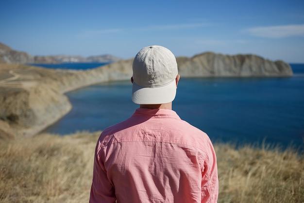 Junger mann, der auf einem gebirgsufer schaut zum meer steht