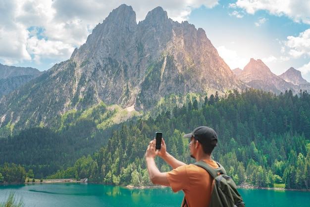 Junger mann, der auf einem grünen berg wandert und die atemberaubende aussicht auf die landschaft bei sonnenuntergang genießt?