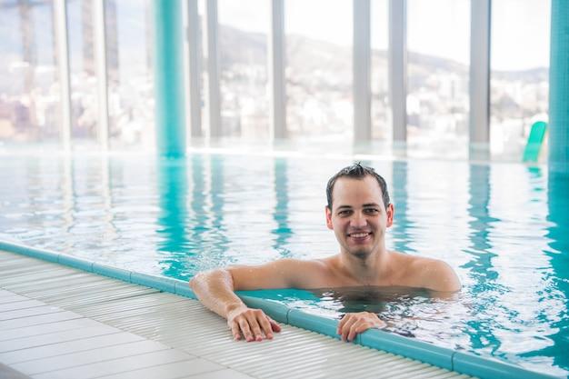 Junger mann, der auf einem luxusdachpool schwimmt und an der kamera im fünf-sterne-hotel-spa lächelt