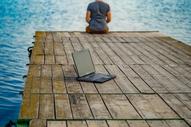 Junger mann, der auf einem pier sitzt und seinen laptop benutzt. arbeit und urlaub.