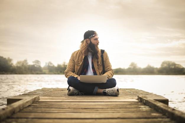 Junger mann, der auf einem pier, unter verwendung seines laptops sitzt