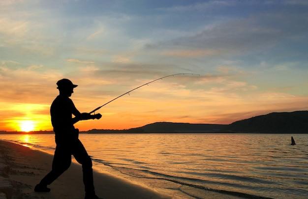 Junger mann, der auf einem see bei sonnenuntergang fischt