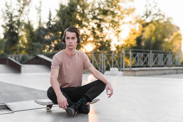 Junger mann, der auf einem skateboard sitzt