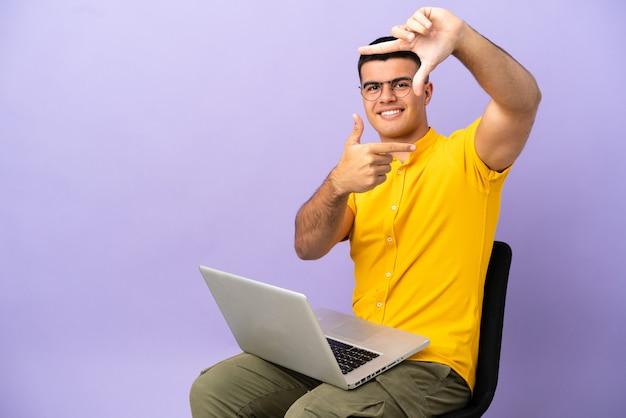Junger mann, der auf einem stuhl mit fokusgesicht des laptops sitzt. rahmensymbol