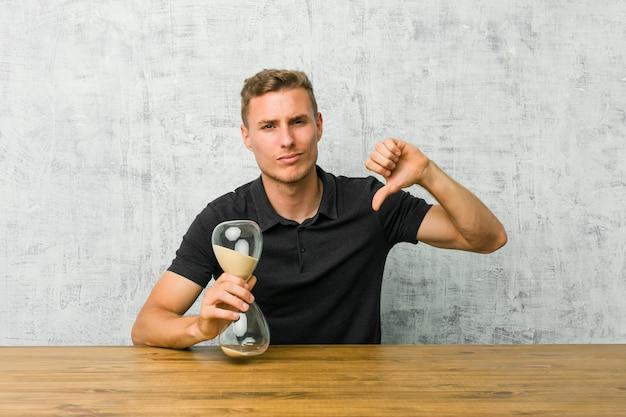 Junger mann, der auf einem tisch einen sandtimer unten zeigt und abneigung ausdrückt