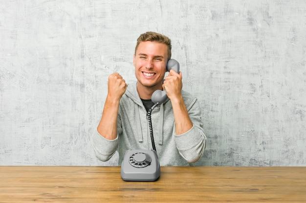 Junger mann, der auf einem weinlese-telefon spricht, das faust hebt, sich glücklich und erfolgreich fühlt