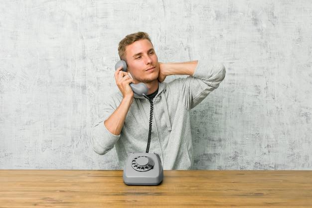 Junger mann, der auf einem weinlese-telefon spricht, das hinterkopf berührt, denkt und eine wahl trifft.