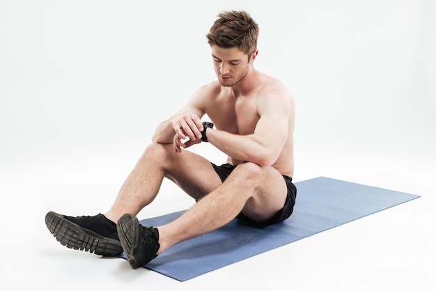 Junger mann, der auf einer fitnessmatte ruht und smartwatch benutzt