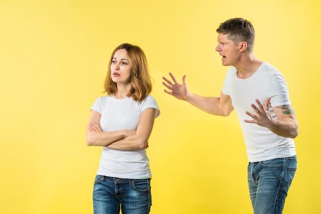 Junger mann, der auf einer verärgerten blonden freundin steht gegen gelben hintergrund schreit