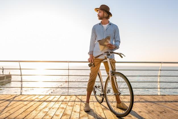 Junger mann, der auf fahrrad durch see in den sommerferien durch das meer auf sonnenuntergang reist und kartensicht mit kamera hält