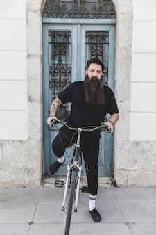 Junger mann, der auf fahrrad vor geschlossener blauer tür sitzt