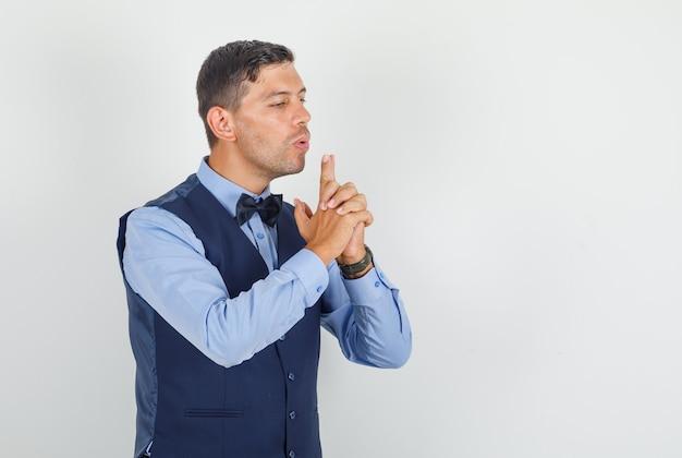 Junger mann, der auf finger bläst, die waffe im anzug zeigen