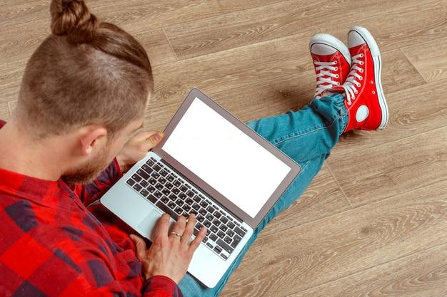 Junger mann, der auf fußboden mit laptop sitzt