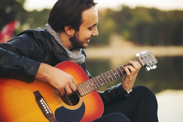 Junger mann, der auf gitarre am see spielt