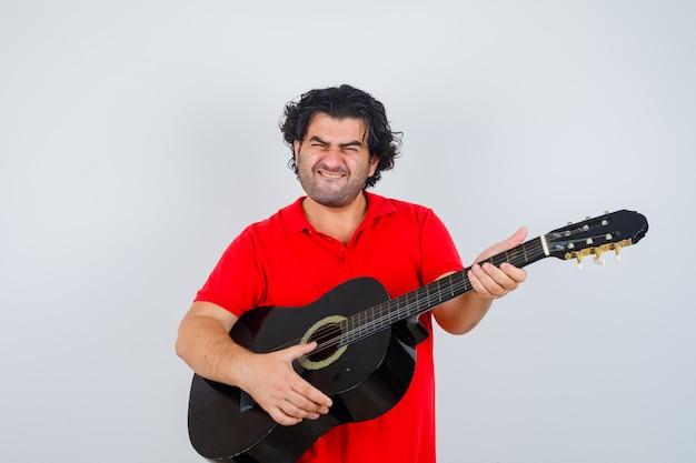 Junger mann, der auf gitarre im orangefarbenen t-shirt spielt und zuversichtlich schaut