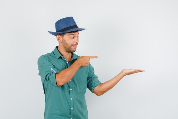 Junger mann, der auf handfläche zeigt, breitete sich im hemd aus