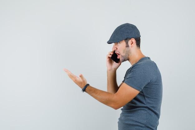 Junger mann, der auf handy in der t-shirt-kappe spricht und wütend schaut