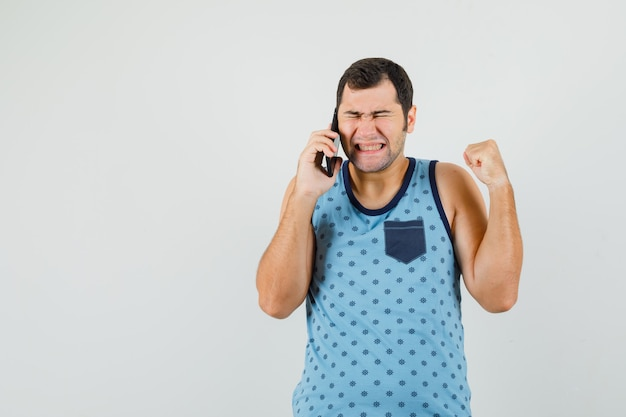 Junger mann, der auf handy spricht, siegergeste im blauen unterhemd zeigend und glückselig, vorderansicht schauend.