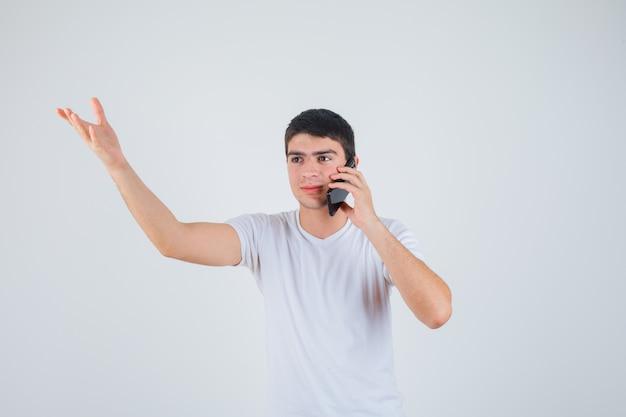 Junger mann, der auf handy spricht, während arm im t-shirt hebt und aufgeregt schaut. vorderansicht.