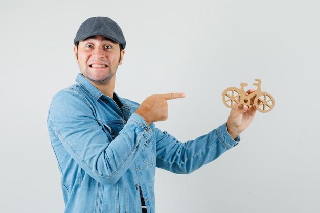 Junger mann, der auf hölzernes spielzeugfahrrad in der kappe, im t-shirt, in der jacke zeigt und glücklich schaut, vorderansicht.