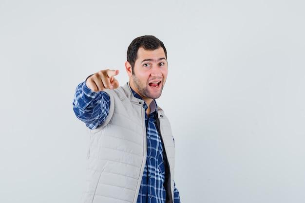 Junger mann, der auf kamera im hemd, ärmellose jacke zeigt und konzentriert schaut