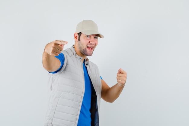 Junger mann, der auf kamera in t-shirt, jacke, mütze zeigt und munter aussieht