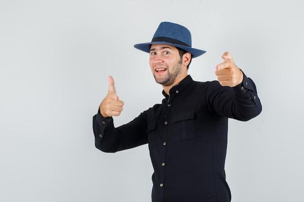 Junger mann, der auf kamera mit gewehrgeste in schwarzem hemd, hut zeigt und fröhlich schaut.