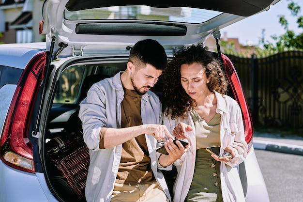 Junger mann, der auf karte im smartphone zeigt, während er seiner frau erklärt, wohin sie sich bewegen werden, und ihren platz zeigt, um für ruhe anzuhalten