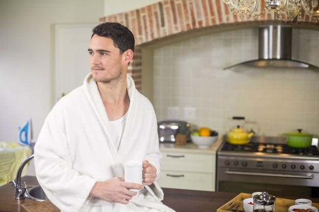 Junger mann, der auf küchenarbeitsplatte sitzt und eine tasse tee hält