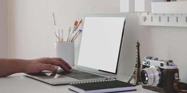 Junger mann, der auf laptop-computer des leeren bildschirms im minimalen künstlerarbeitsplatz schreibt