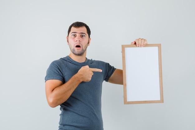 Junger mann, der auf leeren rahmen im grauen t-shirt zeigt und verwirrt schaut