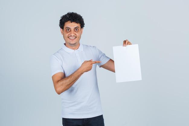 Junger mann, der auf leeres papierblatt im weißen t-shirt, in der hose zeigt und selbstbewusst aussieht, vorderansicht.