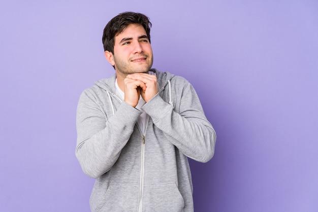 Junger mann, der auf lila raum isoliert ist, hält hände unter kinn, schaut glücklich beiseite.