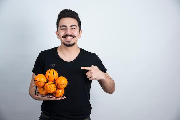 Junger mann, der auf metallischen korb voller orange früchte zeigt.