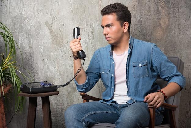 Junger mann, der auf mobilteil schaut und auf stuhl sitzt. hochwertiges foto