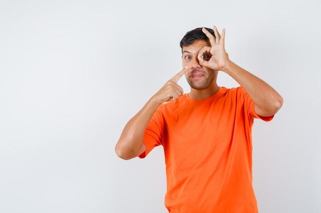 Junger mann, der auf ok zeichen auf auge in orange t-shirt zeigt