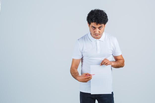 Junger mann, der auf papierblatt mit stift im weißen t-shirt, in der hose zeigt und selbstbewusst aussieht, vorderansicht.