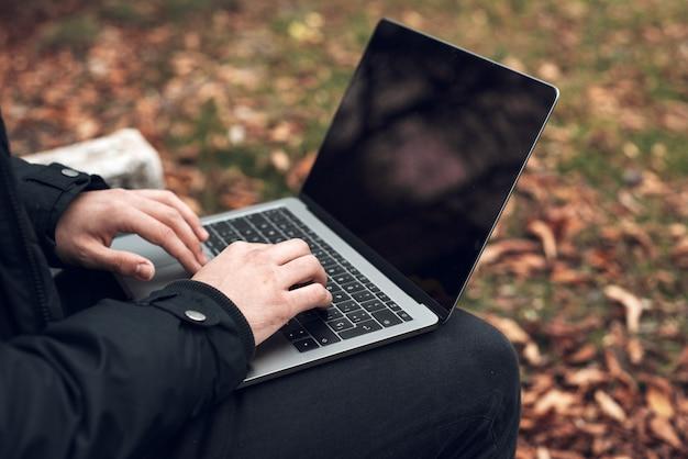 Junger mann, der auf parkbank auf herbst mit laptop sitzt. student, der draußen computer verwendet. nahansicht.