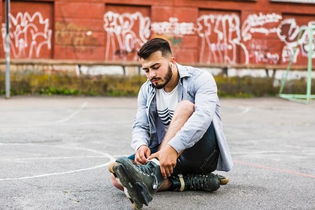 Junger mann, der auf rollerskate am gericht im freien sich setzt