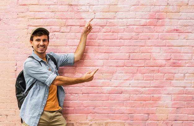 Junger mann, der auf rosa wand zeigt
