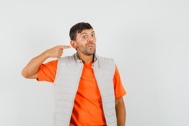 Junger mann, der auf sein ohr in t-shirt, jacke zeigt und seltsam aussieht, vorderansicht.