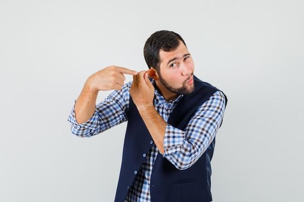 Junger mann, der auf sein ohr zeigt, das durch finger in hemd, weste, vorderansicht gezogen wird.